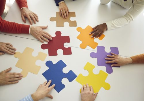 Team of business people joining colorful puzzle pieces as a metaphor for teamwork